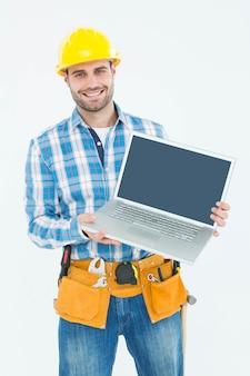 Gelukkige bouwvakker die laptop toont