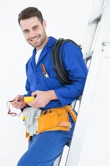 Gelukkige bouwvakker die op ladder leunt