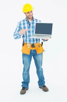 Gelukkige bouwvakker die op laptop richt