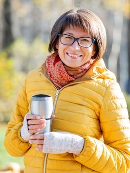 Gelukkige brede glimlachende vrouwen in de heldere gele thermosflessenmok van de jacketisholding. hete thee in koele de herfstdag.