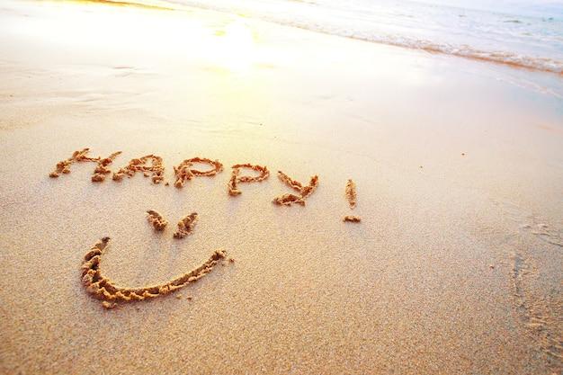 Gelukkige brieven handgeschreven in zand op het strand