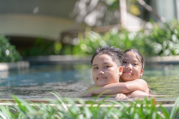 Gelukkige broer en zus spelen in het zwembad, rust en recreatie in de zomer