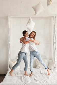 Gelukkige broer en zuster die op bed thuis omhelzen