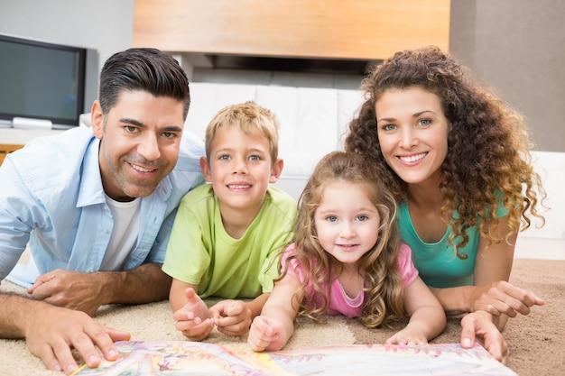 Gelukkige broers en zussen die op het verhalenboek liggen met hun ouders