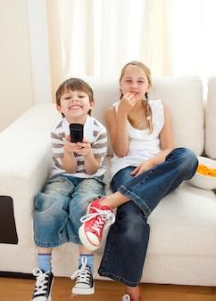 Gelukkige broers en zussen die tv kijken