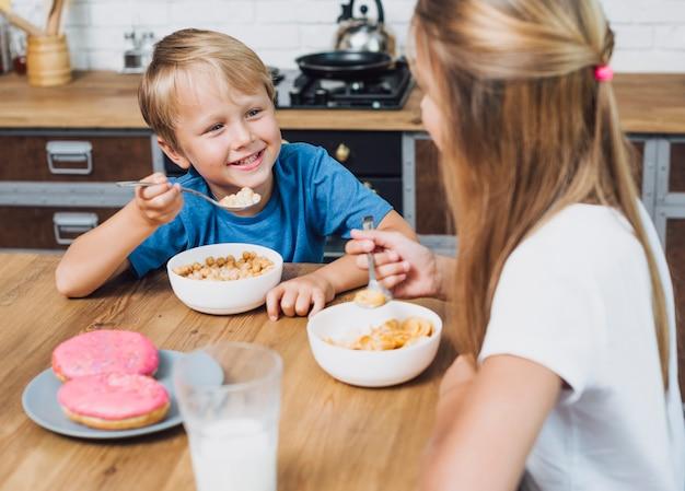 Gelukkige broers en zussen kijken elkaar tijdens het eten