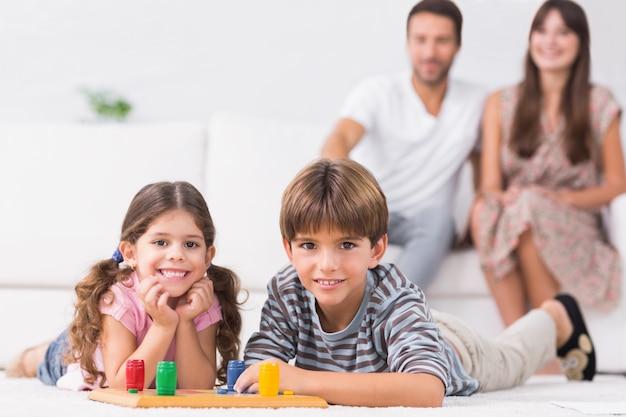 Gelukkige broers en zussen spelen bordspel op de vloer