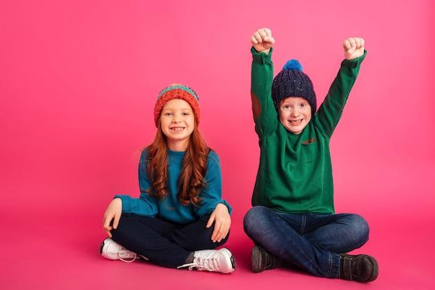 Gelukkige broerzitting met zuster en het maken van winnaargebaar