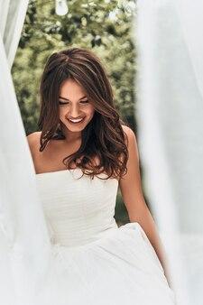 Gelukkige bruid. aantrekkelijke jonge vrouw in trouwjurk die naar beneden kijkt en glimlacht terwijl ze buiten staat