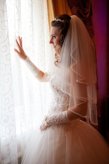 Gelukkige bruid die in venster kijkt
