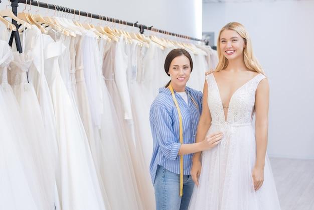 Gelukkige bruid die kleding in winkel probeert