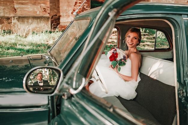 Gelukkige bruid die op haar bruidegom wacht die in de auto zit. feestdagen en evenementen