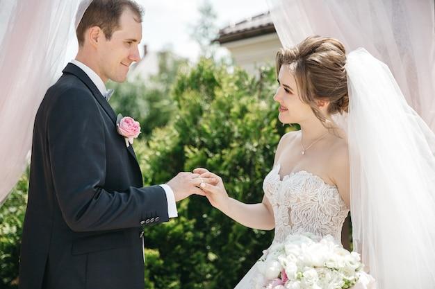Gelukkige bruid draagt een trouwring voor haar man