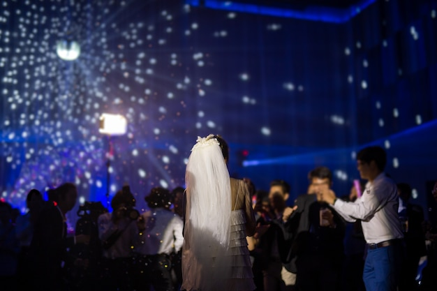 Gelukkige bruid eerste dans op huwelijksfeest met gasten en kleur led-verlichting.