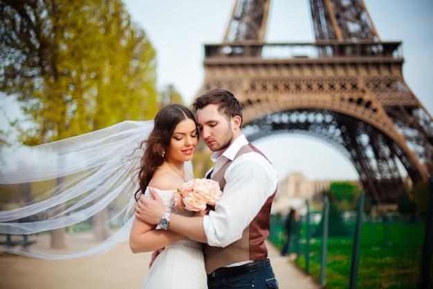 Gelukkige bruid en bruidegom die van hun huwelijk in parijs genieten