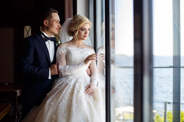 Gelukkige bruid en bruidegom die zachte binnen koesteren. lachende jonggehuwden bij het grote raam. huwelijksfotografie.