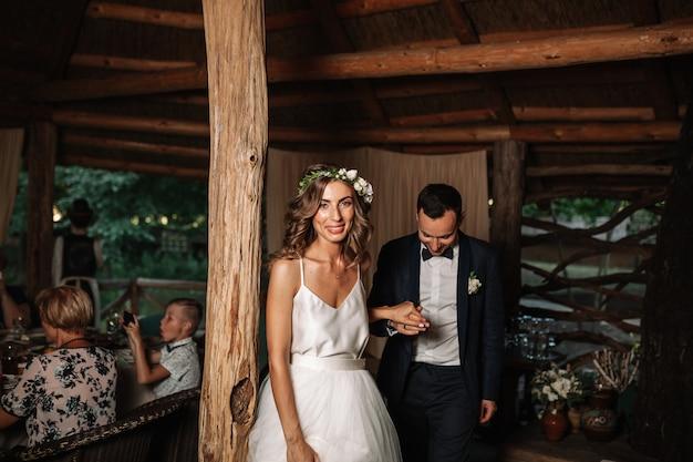Gelukkige bruid en bruidegom en hun eerste dans, huwelijk in het elegante restaurant met een prachtig licht en een atmosfeer