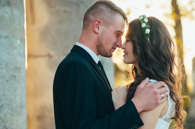 Gelukkige bruid en bruidegom in de buurt van het middeleeuwse paleis op hun trouwdag