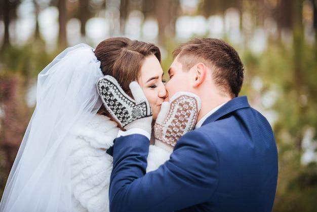 Gelukkige bruid en bruidegom in de winterdag met vuisthandschoenen op hun huwelijk