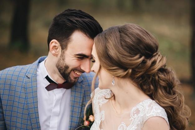 Gelukkige bruid en bruidegom in het bos