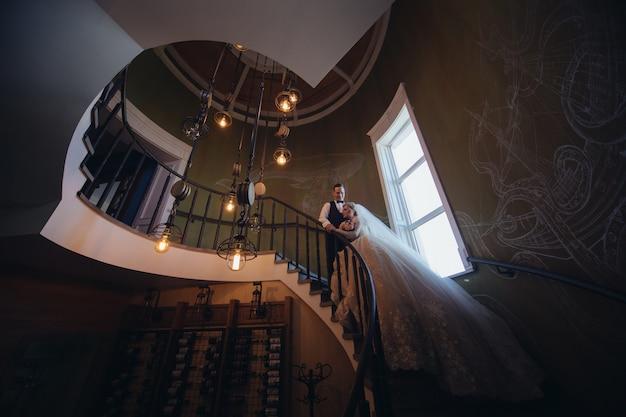Gelukkige bruid en bruidegom kussen en knuffelen op een wenteltrap. portret van liefhebbende jonggehuwden in een prachtig interieur. trouwdag. glimlachend net getrouwd stel