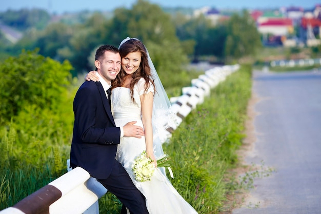 Gelukkige bruid en bruidegom lachen lachend op de weg op een trouwdag.