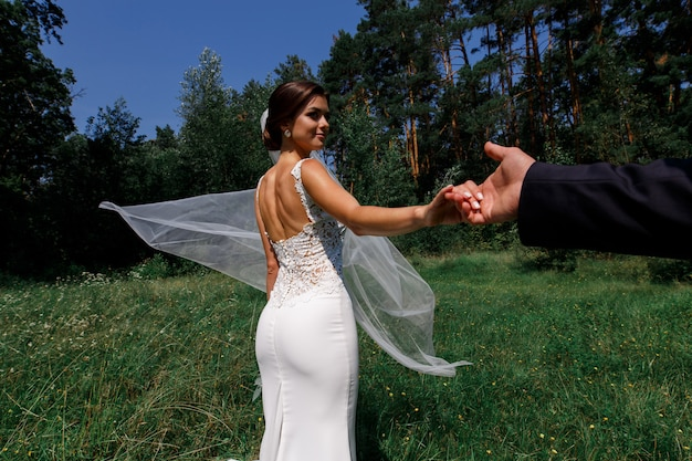 Gelukkige bruid en bruidegom lopen in een groen park