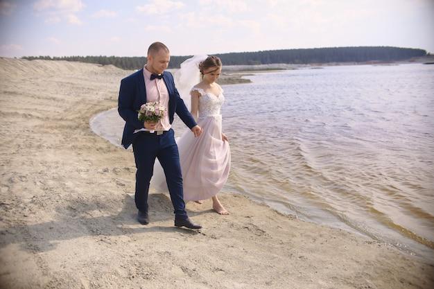 Gelukkige bruid en bruidegom lopen langs de kust meer