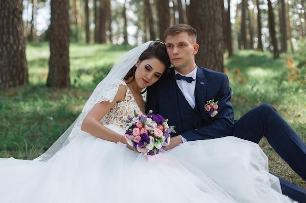 Gelukkige bruid en bruidegom na huwelijksceremonie in aard. tedere gevoelens voor pasgetrouwden in het groene park. trouwdag.