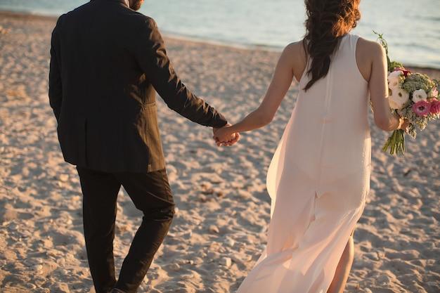 Gelukkige bruid en bruidegom op een prachtig strand bij zonsondergang