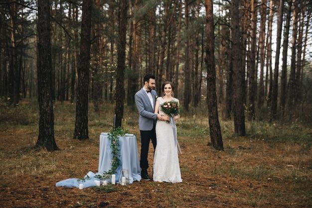 Gelukkige bruid en bruidegom staan in de buurt van de tafel, set voor twee in het bos. herfst. het concept van een romantische date