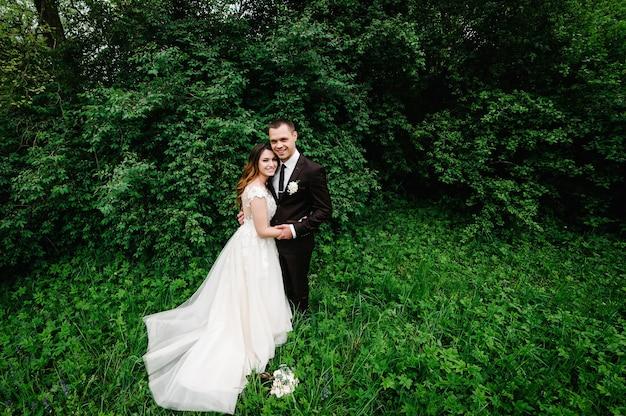Gelukkige bruid en bruidegom trouwen in het groene bos. huwelijksceremonie.
