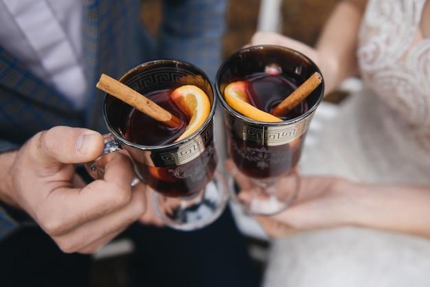 Gelukkige bruid en bruidegomholdingsglazen overwogen wijn