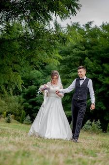 Gelukkige bruid en bruidegomholdingshanden en het lopen in de dag van het tuinhuwelijk. achteraanzicht van charmante stijlvolle pasgetrouwden hand in hand tijdens het wandelen in het park bos, gelukkig huwelijk momenten