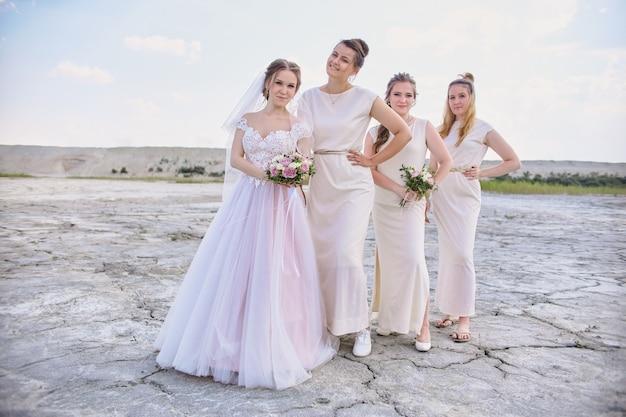 Gelukkige bruid en bruidsmeisjes poseren in de woestijn