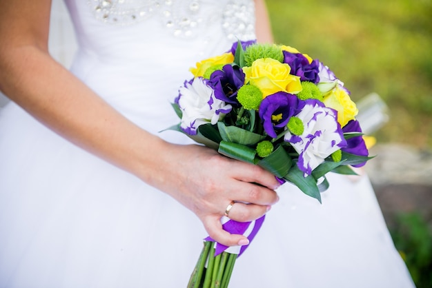 Gelukkige bruid houdt een bruiloft boeket in handen. huwelijksboeket van paarse, gele en witte bloemen in hun handen en een jonge bruid.
