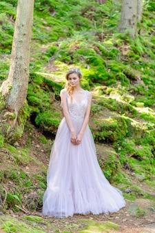 Gelukkige bruid in een roze trouwjurk. boho stijl huwelijksceremonie in het bos.