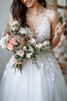 Gelukkige bruid in een trouwjurk met een boeket in haar handen