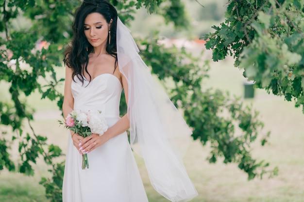 Gelukkige bruid in mooie witte jurk poseren onder boom.