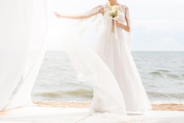 Gelukkige bruid met boquet op het strand.