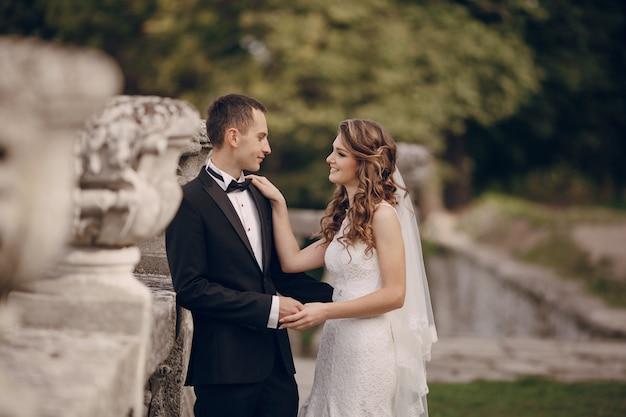 Gelukkige bruid met een hand op de schouder van haar man