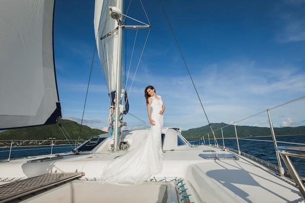 Gelukkige bruid op een jacht. wit jacht met zeilset vaart langs het eiland