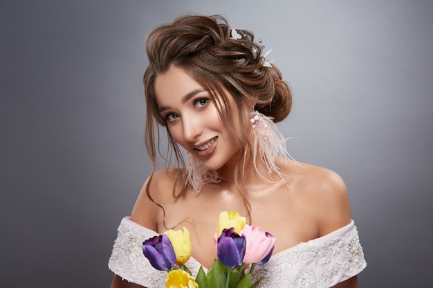 Gelukkige bruid op grijze achtergrond met bloemen glimlachen