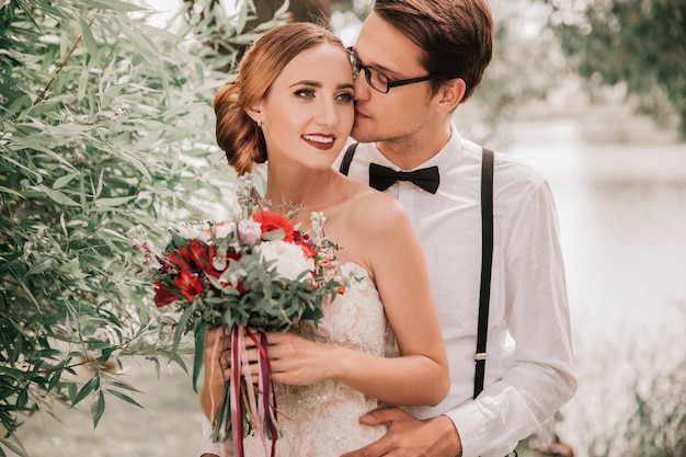 Gelukkige bruidegom die zijn bruid in stadspark kust
