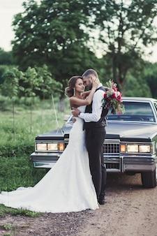 Gelukkige bruidegom en bruid op de oude auto als achtergrond