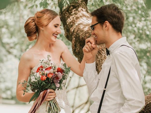 Gelukkige bruidegom kust de hand van zijn bruid tijdens het lopen. romantisch moment