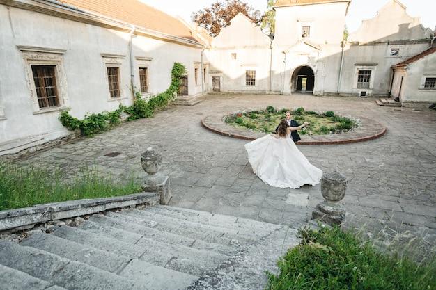 Gelukkige bruiden dansen in de buurt van het kasteel
