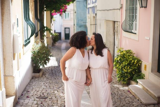 Gelukkige bruiden die teder zoenen