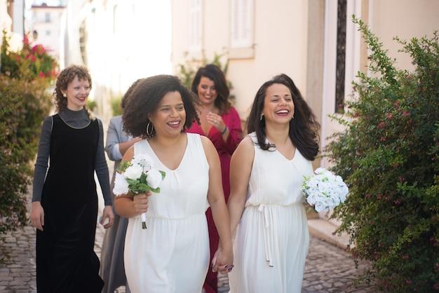 Gelukkige bruiden en gasten op bruiloft. glimlachende vrouwen met boeketten hand in hand ergens heen gaan