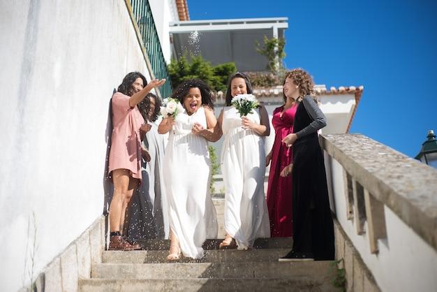 Gelukkige bruiden en gasten op bruiloft. twee vrouwen in witte jurken gaan de trap af. vrouwelijke gasten die rijst naar hen gooien